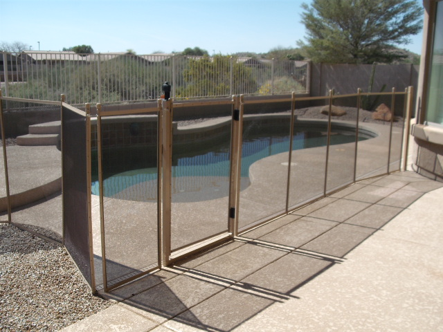 Mesh pool fence in desert sand decking and ground install